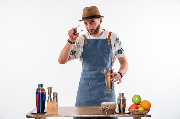 Barman masculino fazendo uma bebida em uma coqueteleira na parede branca bar de bebidas alcoólicas em bar noturno