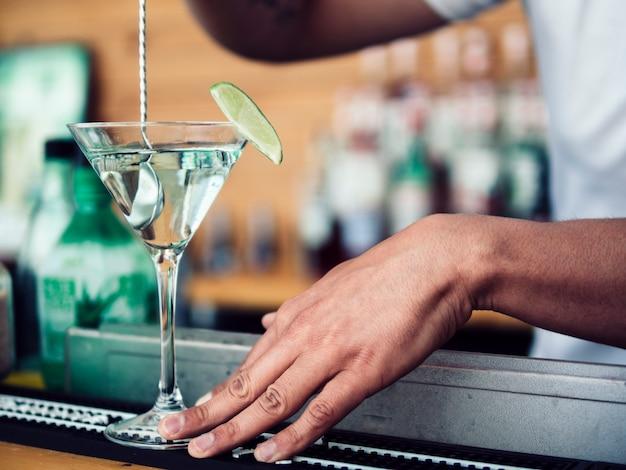 Barman masculino, mexendo o coquetel no copo de martini