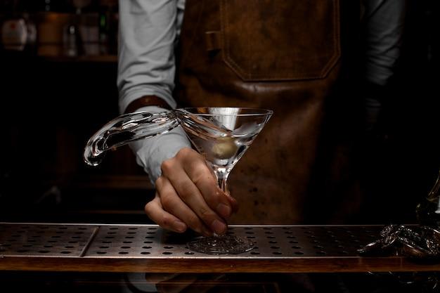 Barman masculino profissional que mistura uma bebida alcoólica transparente no copo de martini com uma azeitona