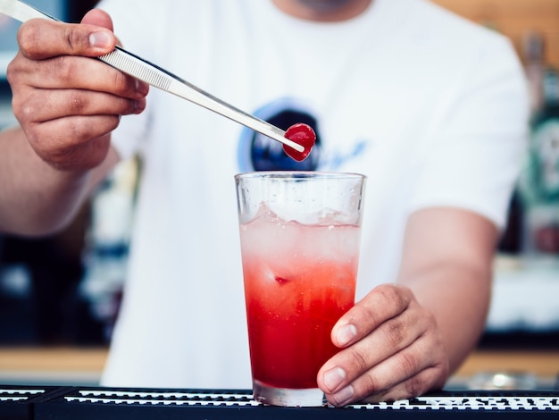 Barman masculino que decora a bebida com cereja