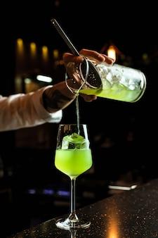 Barman masculino que prepairing um cocktail, derramando uma bebida verde de um copo de mistura através de um filtro em um copo de vinho com um cubo de gelo