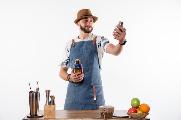 Barman masculino segurando coquetéis em uma parede branca bar de bebidas alcoólicas em bar noturno