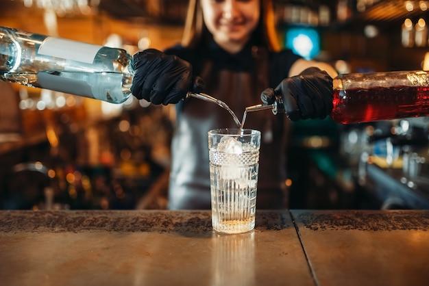 Barman mulher misturando coquetel com álcool em bar