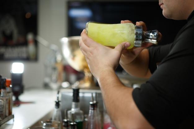 Barman no trabalho preparando coquetéis. agitando a coqueteleira.