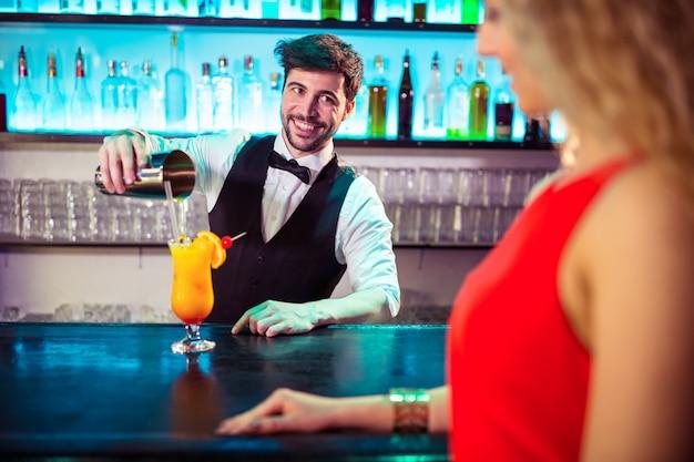 Barman, olhando para a mulher enquanto derramar coquetel no copo