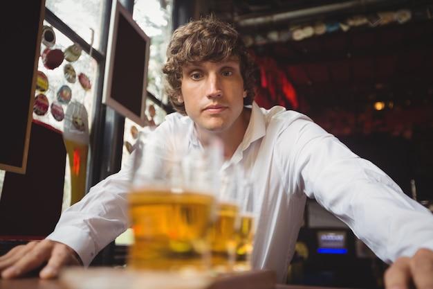 Barman, olhando para copos de cerveja