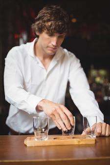 Barman, organizando o copo de cerveja na bandeja no balcão de bar