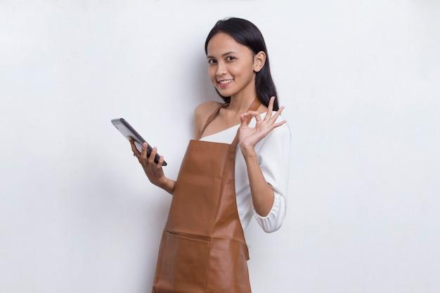 Barman ou garçonete jovem asiática usando smartphone móvel isolado no fundo branco