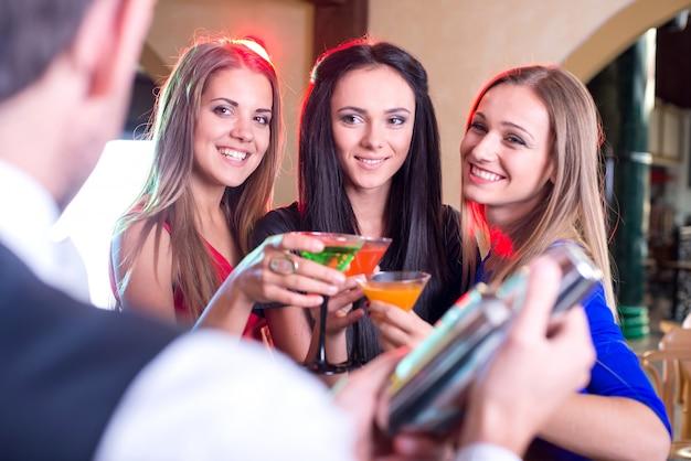 Barman prepara deliciosos cocktails para meninas bonitas.