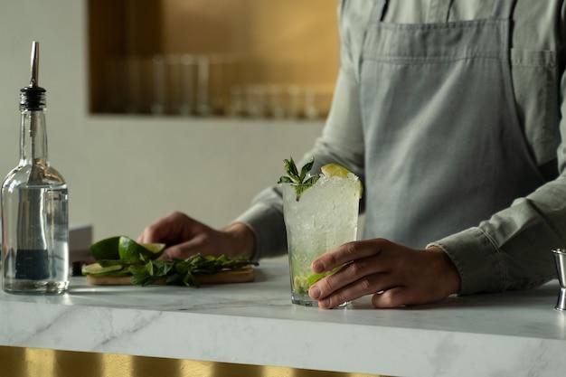 Barman preparando e misturando coquetéis no balcão do bar mojito coquetel servido no bar do restaurante