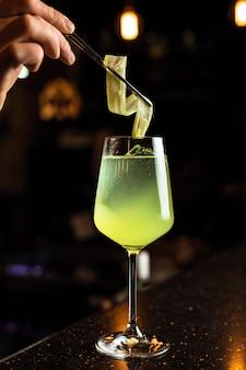 Barman preparando um coquetel, adicionando guarnição de aipo em um copo de vinho com uma bebida gelada de cor verde