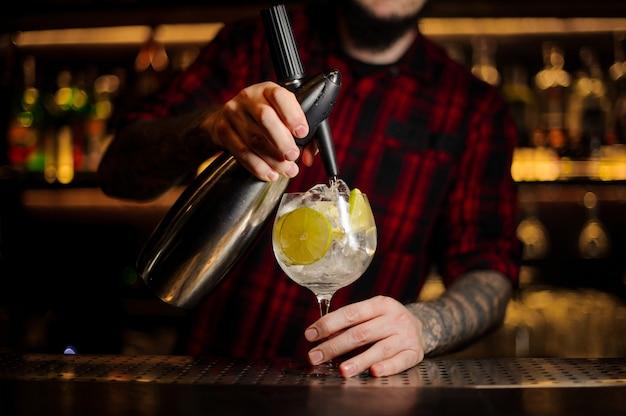 Barman preparando um coquetel azedo fresco com limão usando equipamento profissional no balcão do bar