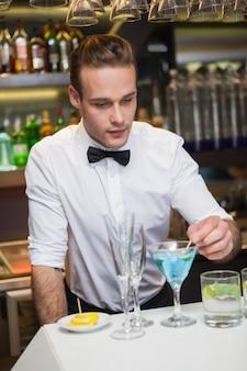 Barman preparando uma bebida no balcão de bar