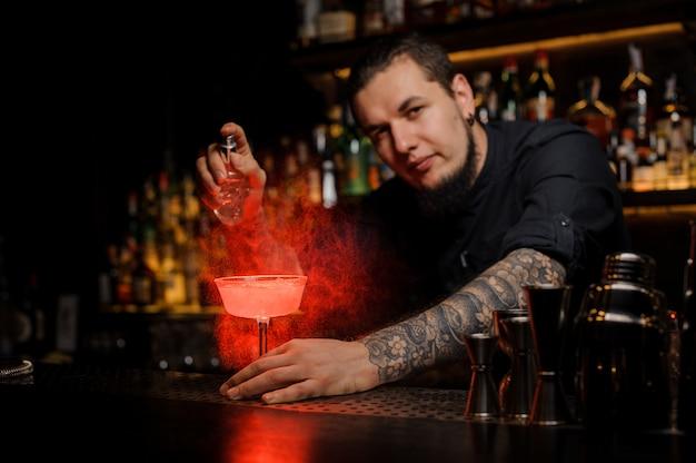 Barman profissional aspersão de cor vermelha amarga em um copo de cocktail