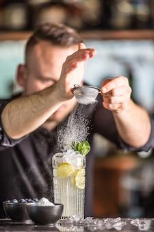 Barman profissional fazendo bebida alcoólica com açúcar de frutas e ervas.