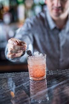 Barman profissional fazendo coquetéis alcoólicos.
