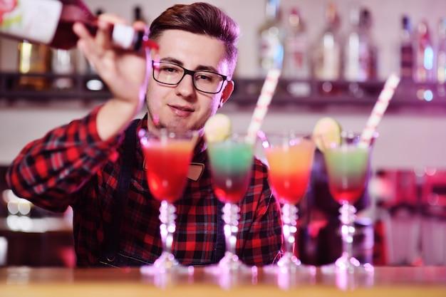 Barman profissional prepara e mistura cocktails derramando xarope vermelho de uma garrafa de um bar em uma boate