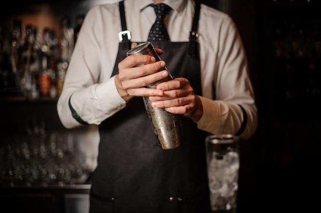 Barman profissional, segurando uma coqueteleira de aço