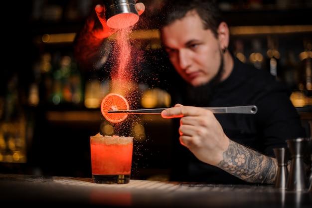 Barman profissional tatuado adicionando especiarias em pó em um copo de coquetel com uma fatia de limão