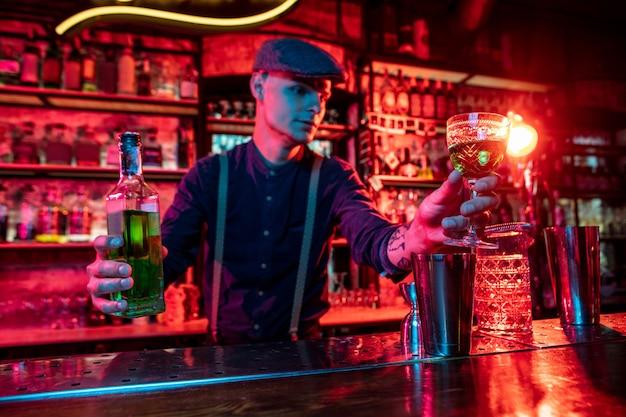 Barman propondo coquetéis alcoólicos, shots e bebidas aos convidados em luz neon multicolorida
