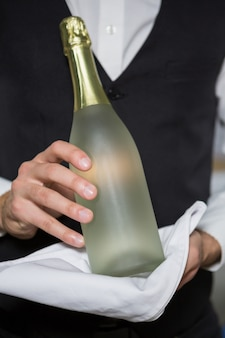 Barman, segurando a garrafa de champanhe em bar
