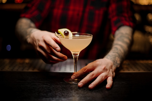 Barman segurando cocktail suculento fresco com laranja e cereja