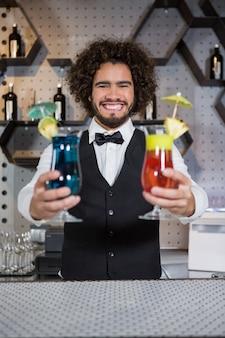 Barman, segurando dois copo de cocktail no bar balcão