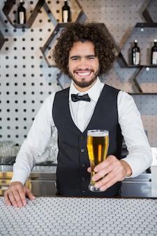 Barman, segurando o copo de cerveja no balcão de bar