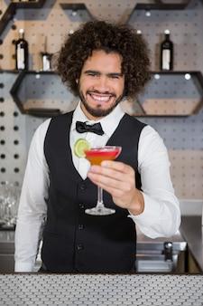 Barman, segurando o copo de cocktail no balcão de bar
