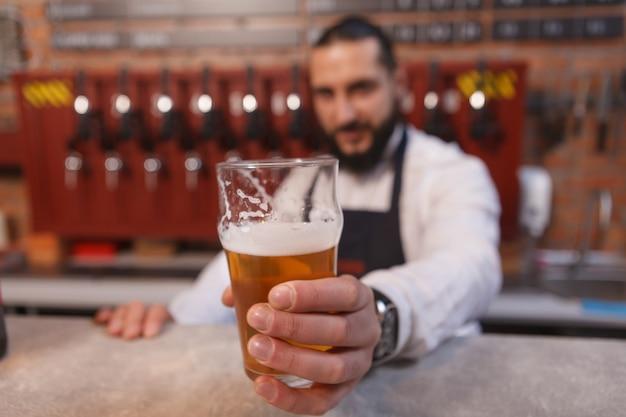 Barman segurando um copo de cerveja, trabalhando em seu pub