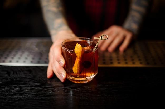 Barman segurando um copo de coquetel com uísque decorado com casca de laranja no balcão do bar