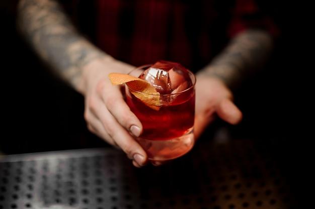 Barman, segurando um copo de coquetel de uísque fresco forte