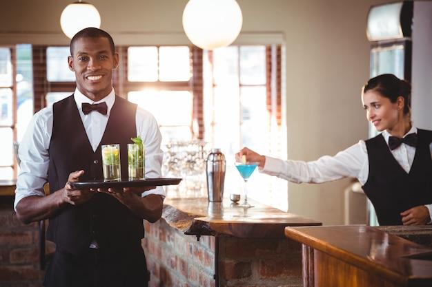 Barman, segurando uma bandeja com dois copo de cocktail