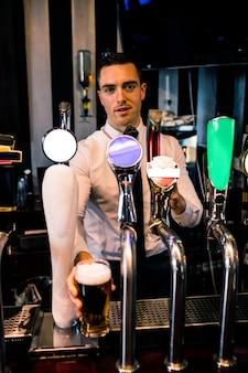Barman serve uma caneca de cerveja em um bar