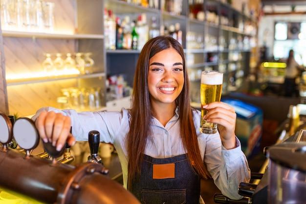 Barman servindo chope no balcão do bar, prateleiras cheias de garrafas com álcool ao fundo