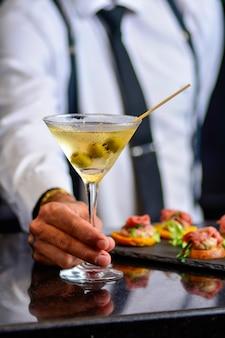Barman servindo coquetel e aperitivo em um bar escuro - foco seletivo
