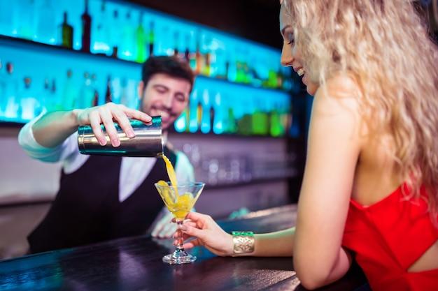 Barman, servindo coquetel para jovem no balcão