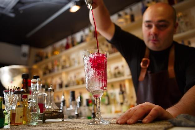Barman servindo coquetel vermelho em um copo no bar