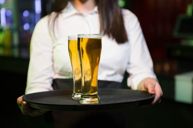 Barman, servindo dois copos de cerveja em bar