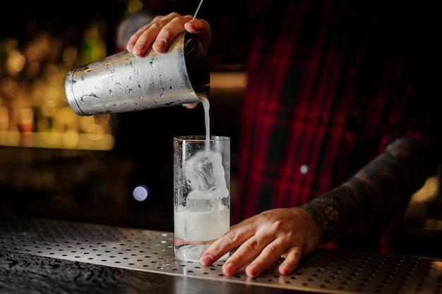 Barman servindo limonada da coqueteleira em uma taça de coquetel com cubos de gelo no bar