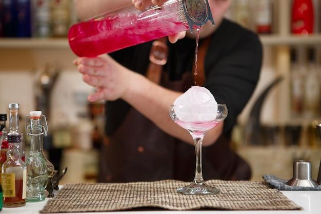 Barman servindo um coquetel rosa