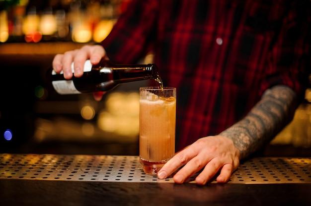 Barman servindo uma bebida alcoólica em um coquetel singapore sling da garrafa no balcão do bar