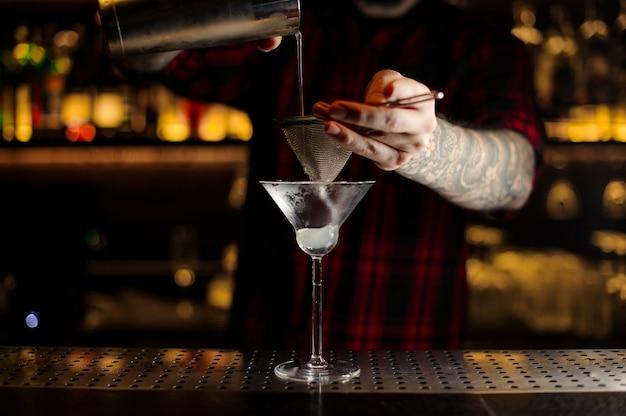 Barman servindo uma bebida saborosa e fresca em um copo de coquetel usando um shaker e um coador