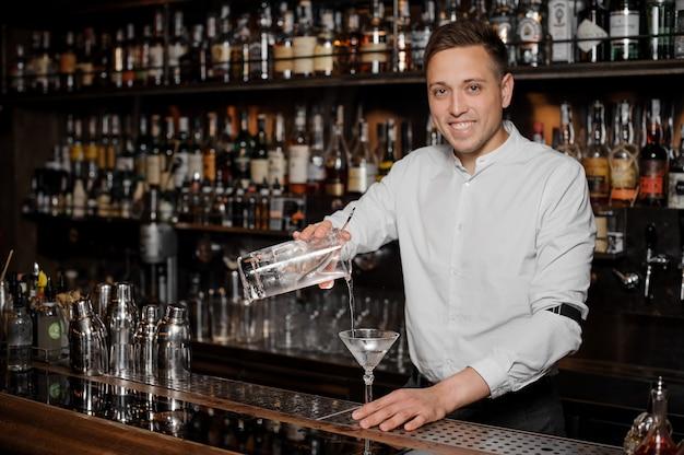Barman sorridente, adicionando uma bebida alcoólica no copo de martini