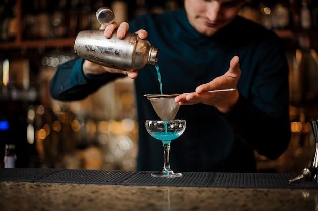 Barman sorridente derramando bebida fresca com licor azul de um agitador em um copo usando filtro