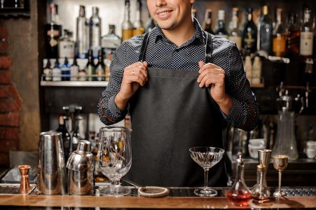 Barman sorridente em pé atrás do balcão de bar com um equipamento de bar
