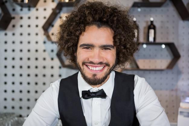 Barman sorridente em pé no balcão de bar