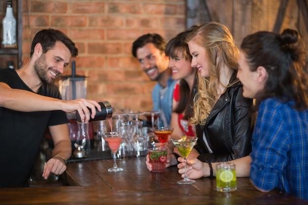 Barman sorridente servindo bebida para clientes