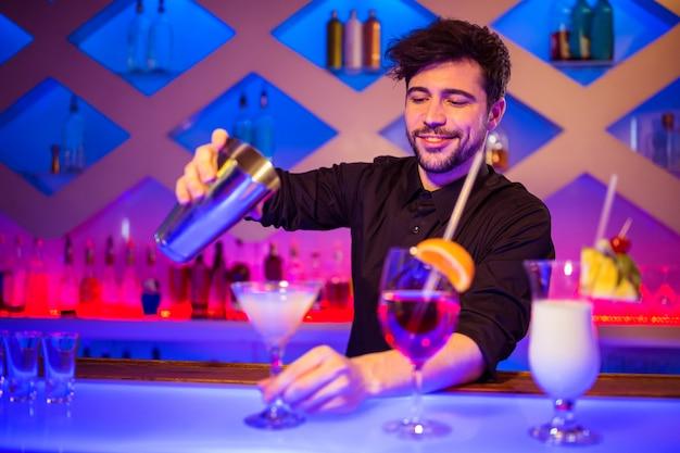 Barman, sorrindo enquanto prepara cocktail