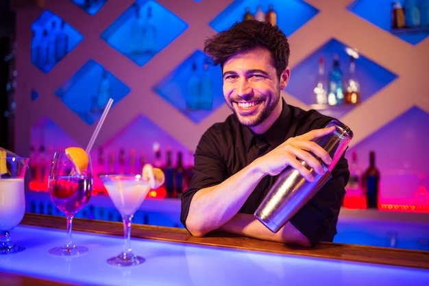 Barman sorrindo enquanto segura coqueteleira